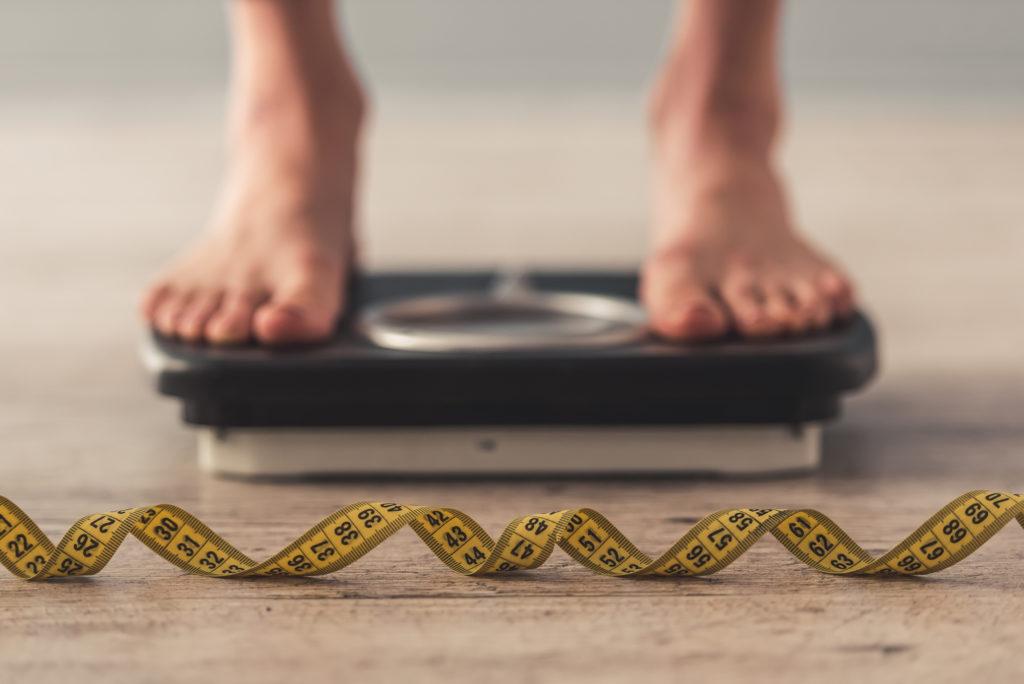Gesunde Fette: angeschnittenes Bild von Waage und Maßband