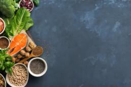 Gesunde Fette: Leinöl, Lachs, Leinsamen, Avocado auf einem Tisch
