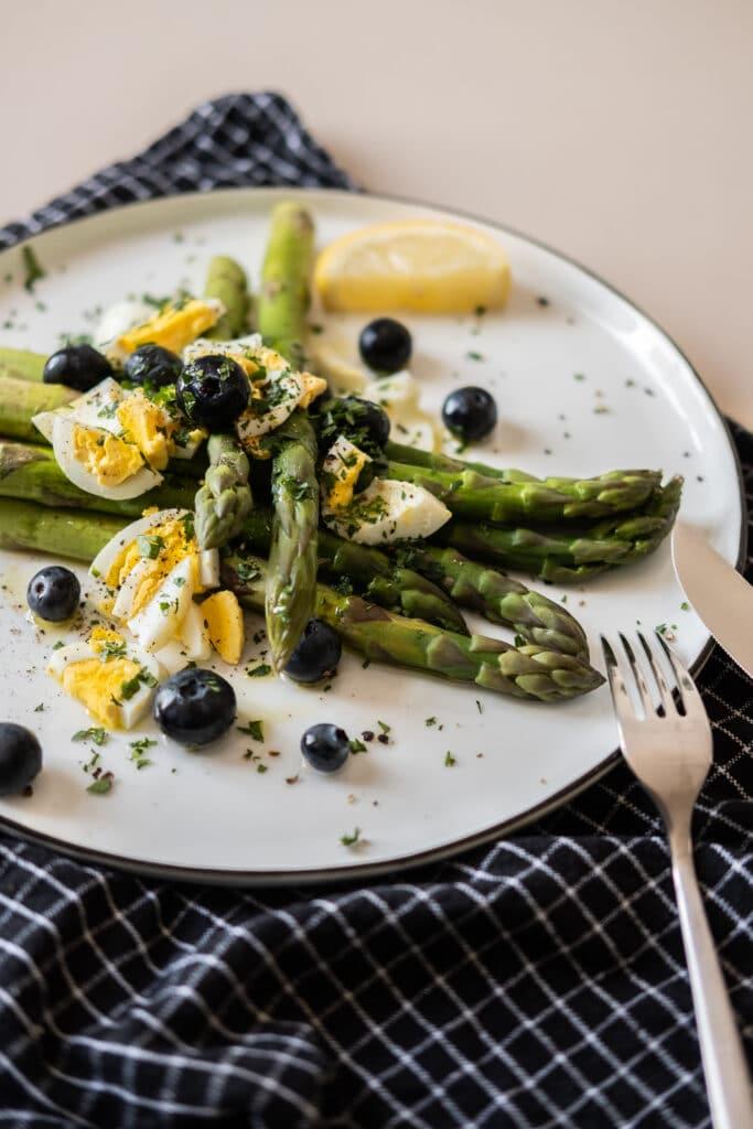 Rezept grüner Spargel mit Ei und Blaubeeren auf Teller