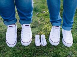 Nachwuchs erwartet - Babyschuhe neben Schuhe der Eltern 1